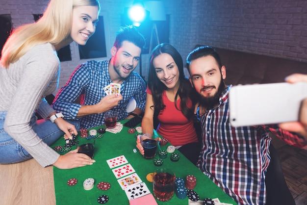 Молодые люди играют в покер за столом и делают селфи.