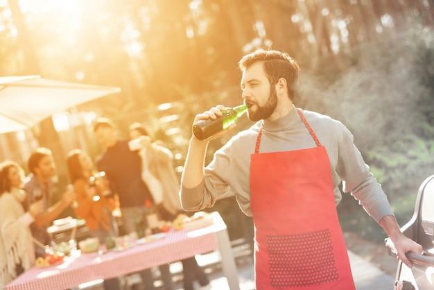 赤いエプロンの男は楽しい時を過すし、食べ物を調理し、アルコールを飲む