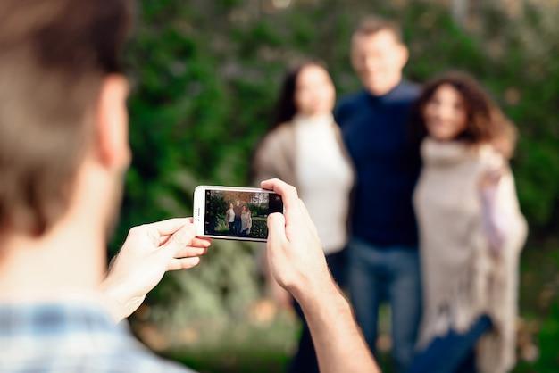 男がスマートフォンで友達の写真を撮ります。