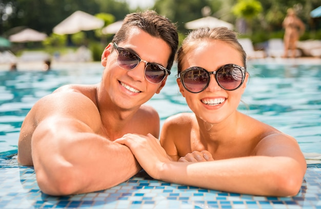 リゾートのプールでカップル。カメラを見てください。