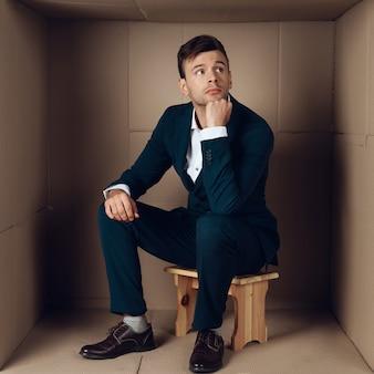 段ボール箱に黒いスーツの青年実業家。
