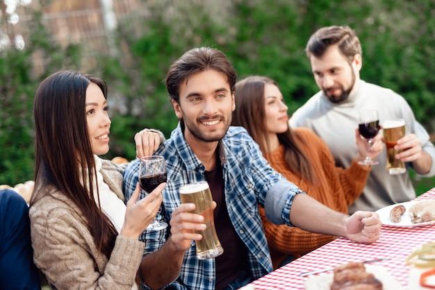 その男は微笑んで彼のグラスからビールを飲みます。