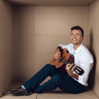 段ボール箱でギターを弾くシャツの若い男。