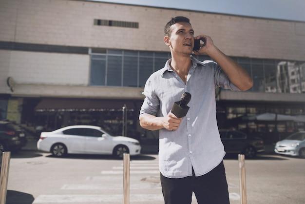 Корреспондент на улице разговаривает по телефону.