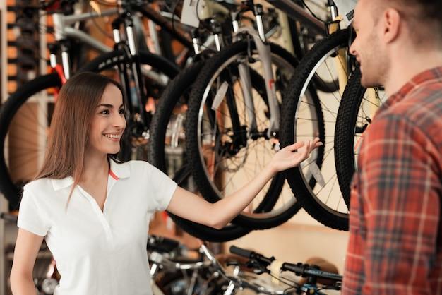 女の子のコンサルタントが自転車屋でバイヤーを見せます。