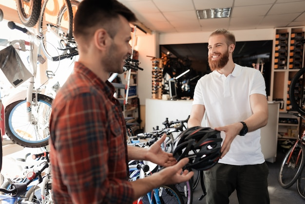 Крупный план счастливого консультанта дает шлем покупателю.