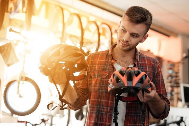Парень внимательно смотрит на шлемы для езды на велосипеде.
