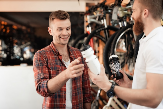 売り手は、男が自転車用の水筒を選ぶのを助けます。
