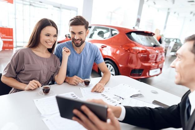 若い家族が車のショールームで新しい車を選ぶ