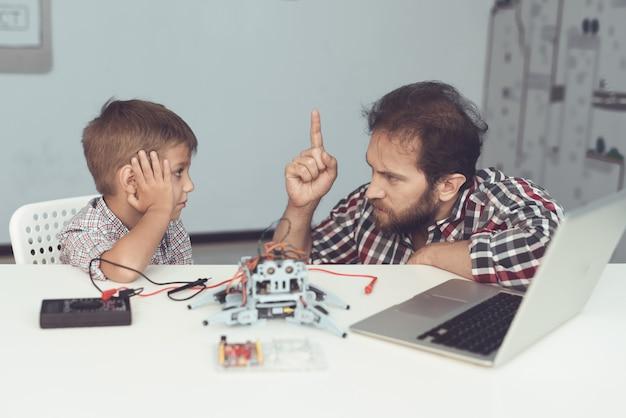 あごひげを生やした父親が自宅でロボットと動揺の息子を助けます。