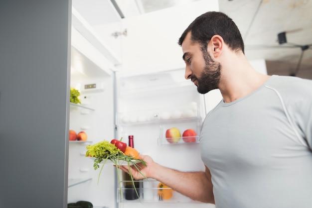 スポーティな男が台所に立ち、新鮮に服用します。