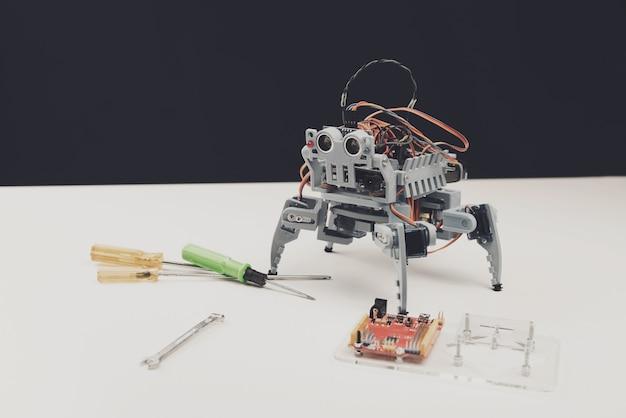 閉じる。テーブルの上のツールと小さな灰色のロボット。