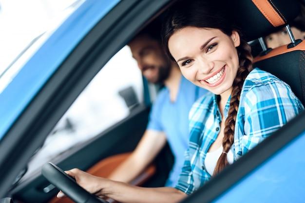 女性が新しい車の運転席に座っています。