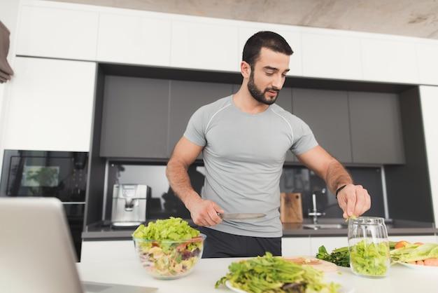 スポーティな男が台所でサラダを準備しています。