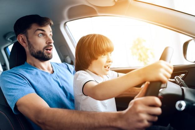 小さな息子を持つ男が車のホイールに座っています。