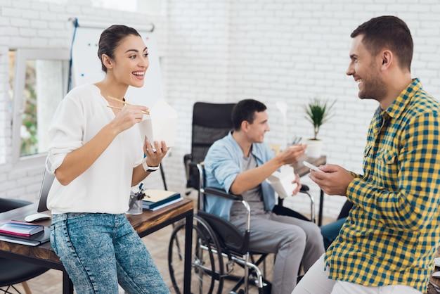 Молодые люди обедают с азиатской едой в офисе.
