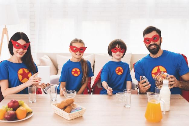 スーパーヒーローのスーツを着た子供と両親。