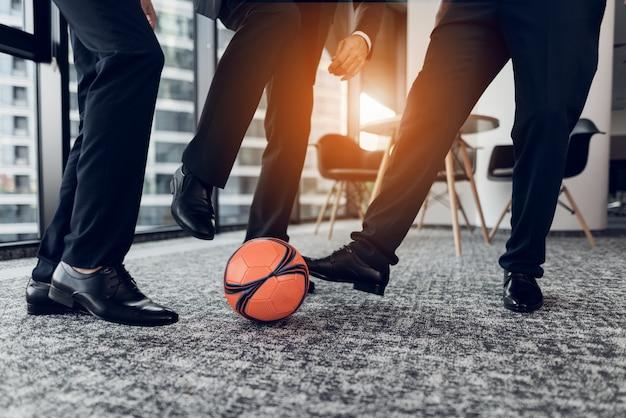 Закройте мужчины в строгих брюках и черных туфлях играют в мяч.