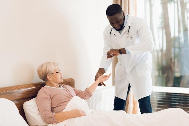 医師は特別養護老人ホームで高齢の患者を診察します。