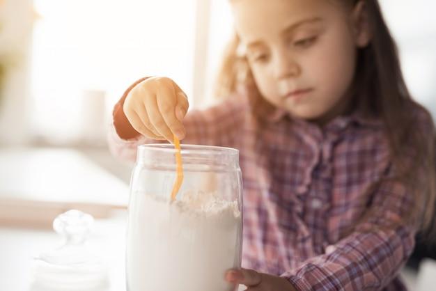 その少女は何かを調理しようとしています。