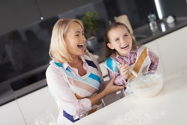 祖母と孫娘が料理を準備しています。