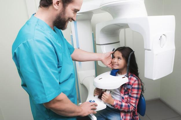 男性医師が少女のあごのレントゲンを撮ります。