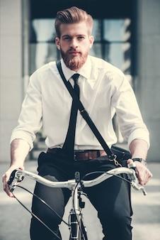Бизнесмен в классическом костюме и с сумкой едет на велосипеде.