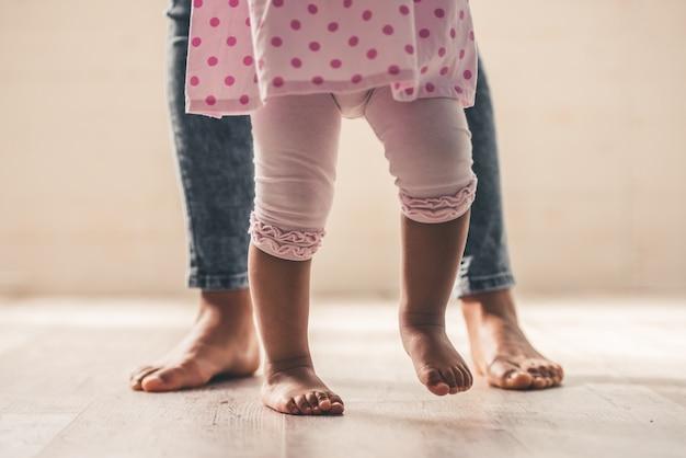 アフロアメリカンママと彼女のかわいい女の赤ちゃんの足。