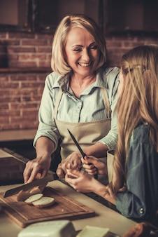 おばあちゃんと孫娘はサンドイッチを作っています。