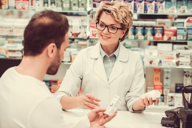 Фармацевт предлагает клиенту лекарство и улыбается.