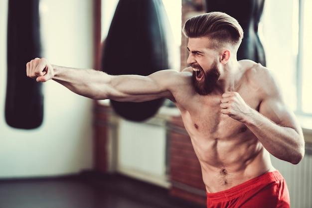 裸の胴体を持つボクサーは、ファイトクラブでパンチを練習しています。