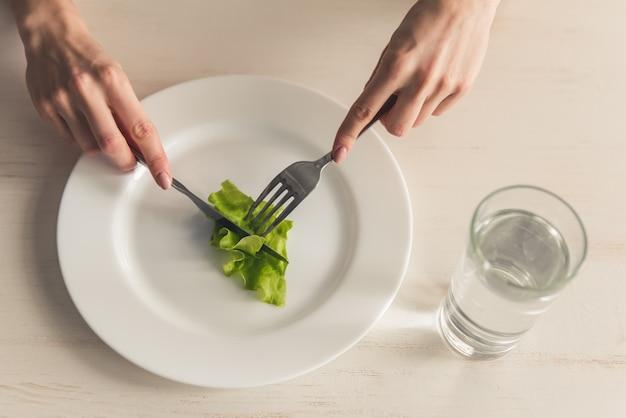 摂食障害。レタスを食べる少女の画像をトリミングしました。