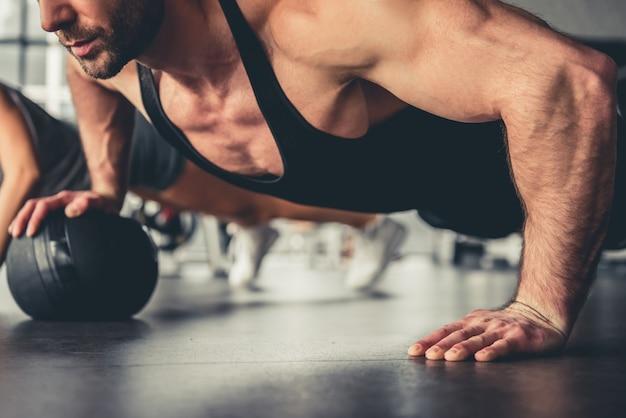 魅力的なスポーツの人々は腕立て伏せをしています。