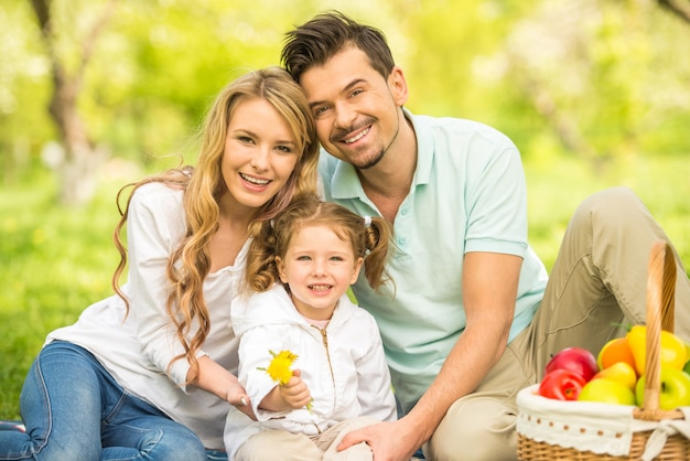 屋外のピクニックを持つ若い家族。
