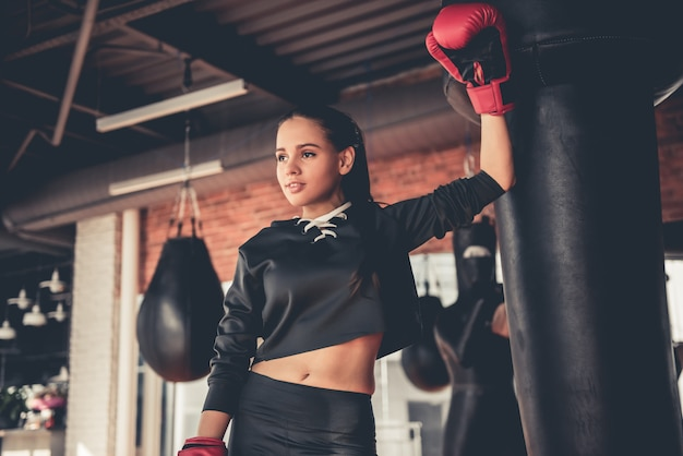 ボクシンググローブの魅力的なスポーツ少女は練習しています。