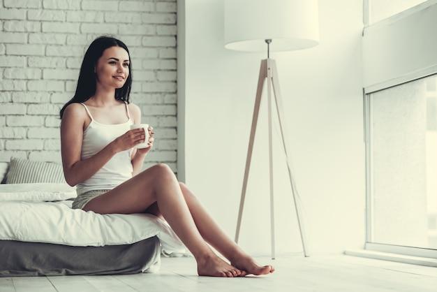 美しい少女はカップを保持していると休んでいる間笑っています。
