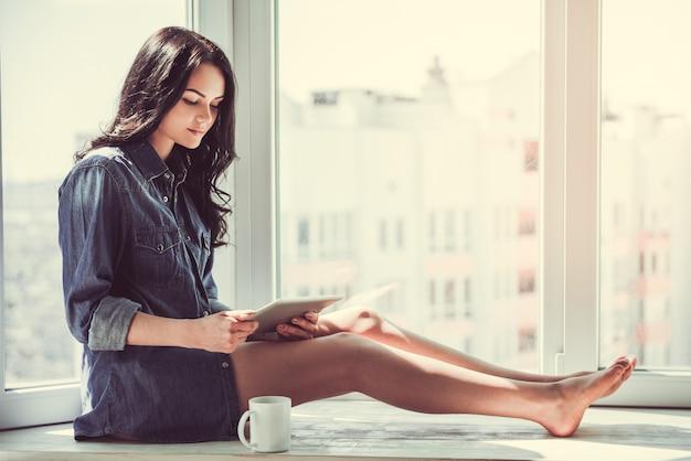 ジーンズシャツの美しい若い女性はデジタルタブレットを使用しています。
