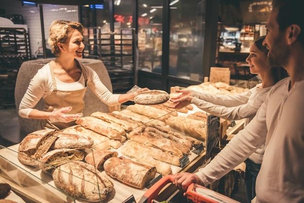 美しい労働者はパンを提供しながら笑っています。