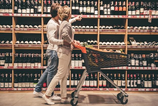 美しいカップルは話しているとワインを選んでいる間笑っています。
