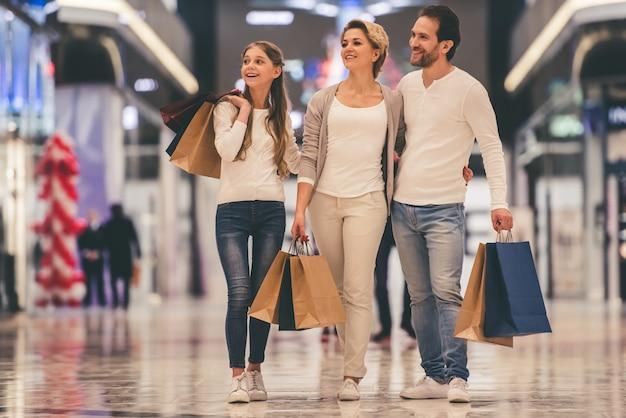 両親とその娘は買い物袋を持っています。