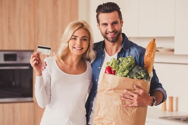 美しい若いカップルは紙袋を持っています。