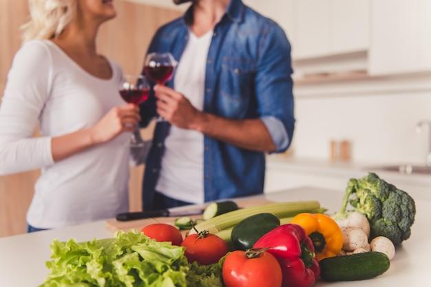 美しいカップルが台所で料理をしながらワインを飲みます。