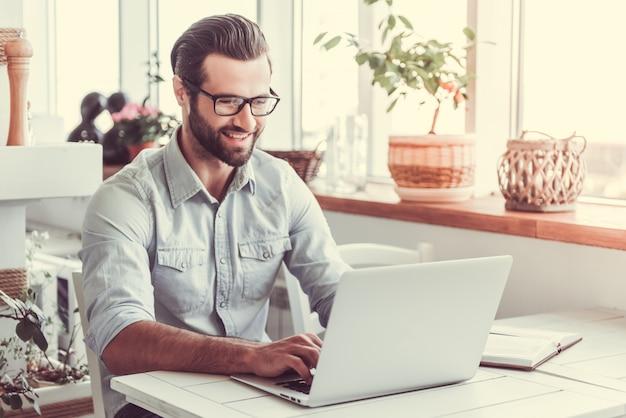 眼鏡でハンサムなビジネスマンはラップトップを使用しています。