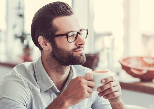 Молодой бизнесмен в очки пьет кофе.