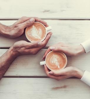 一杯のコーヒーを保持している愛のカップルの画像をトリミングしました。