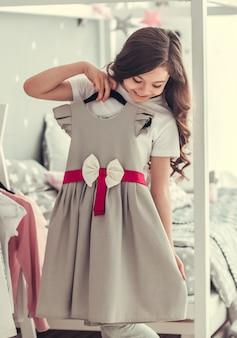 かわいい女の子は美しいホリデードレスを試着しています。