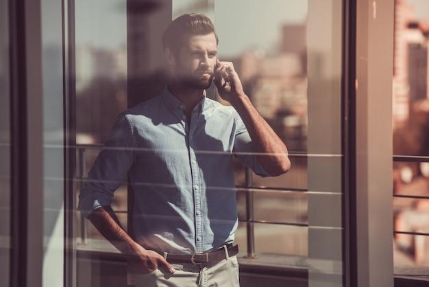 Отражение в окне бизнесмена, разговаривает по телефону.
