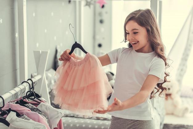 かわいい女の子は美しいチュールスカートを調べています。