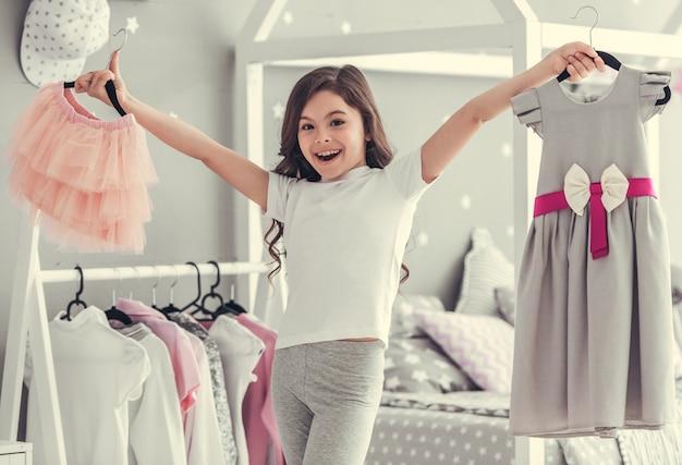 かわいい女の子は美しいチュールスカートとドレスを持っています。
