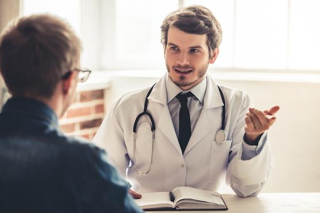 白衣のハンサムな医者は彼の患者に話しています。
